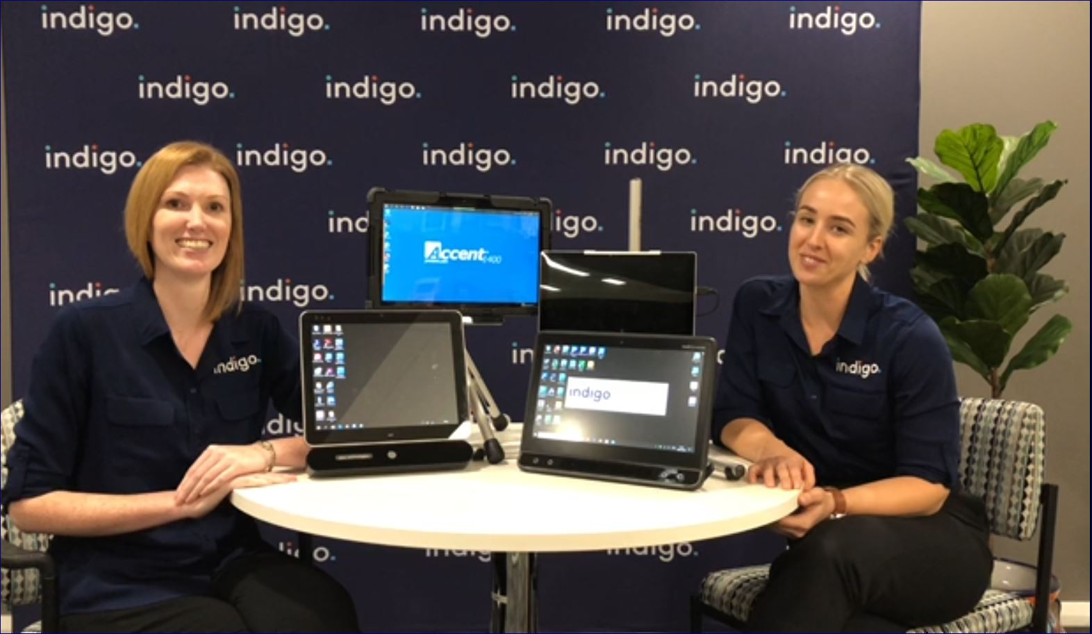 Speech Pathologists Tanith and Michelle with some Eye Gaze devices, Smiling professional women wearing Indigo uniforms seated at a table with AAC AT